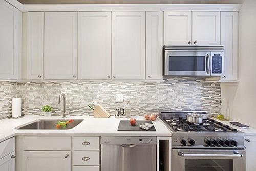 Bếp mới khiến bất kỳ bà nội trợ nào cũng thích mê với gam màu trắng sáng bắt mắt cùng nội thất hiện đại và gạch ốp tường sạch sẽ