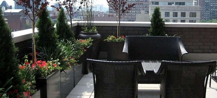 Bộ bàn ghế cùng tông màu với bồn trồng cây và gạch ốp lan can tạo nên vẻ đẹp hài hòa, thông nhất cho vườn trên sân thượng.