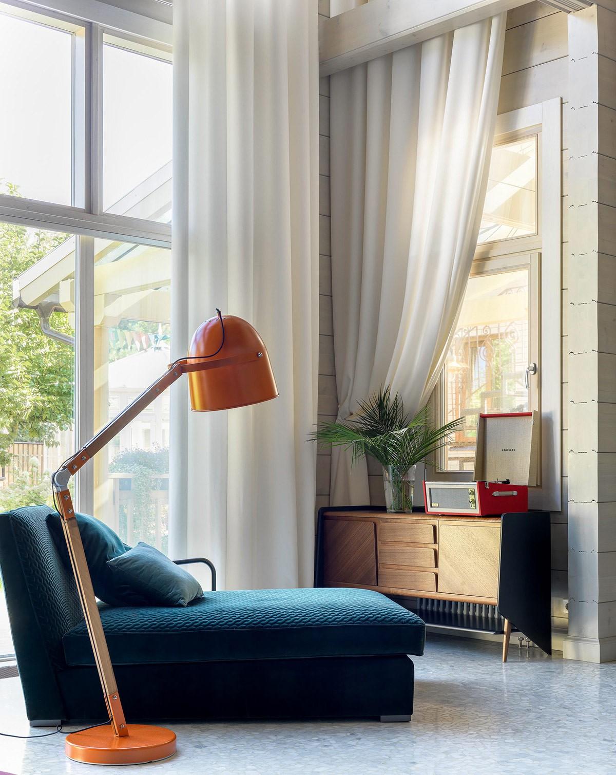 Hình ảnh một góc phòng khách với ghế tựa êm ái, đèn sàn màu cam, tủ kệ lưu trữ