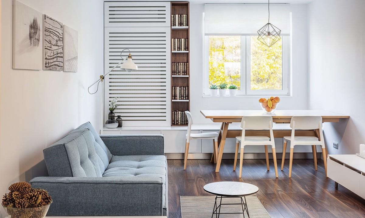 Hình ảnh phòng ăn liền kề phòng khách với ghế sofa ghi xám, bàn ăn màu trắng đặt cạnh khung cửa sổ