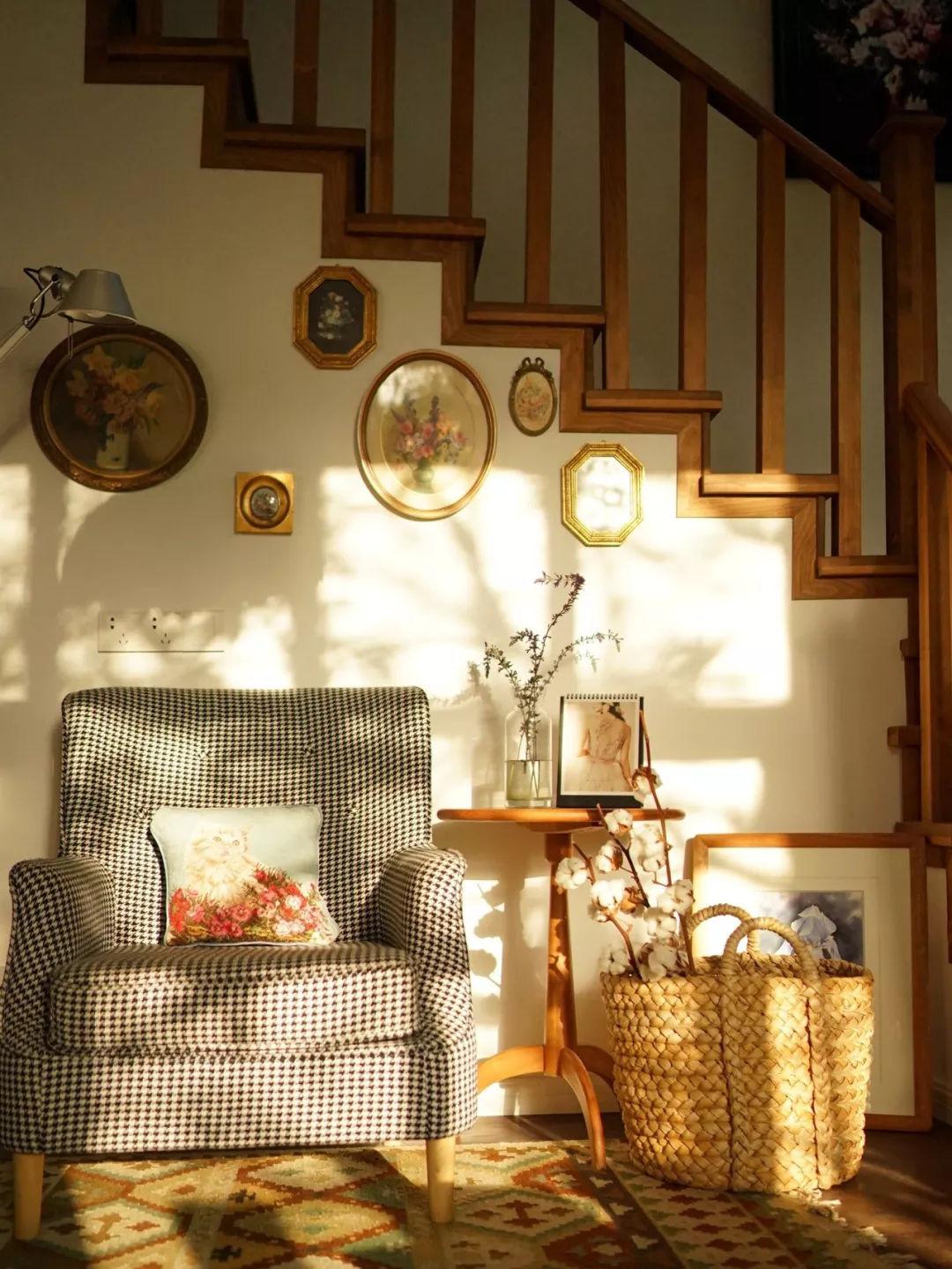 Hình ảnh góc đọc sách với ghế bành bọc nệm kẻ caro, bàn trà gỗ hình tròn, giỏ cói đan, tranh treo tường