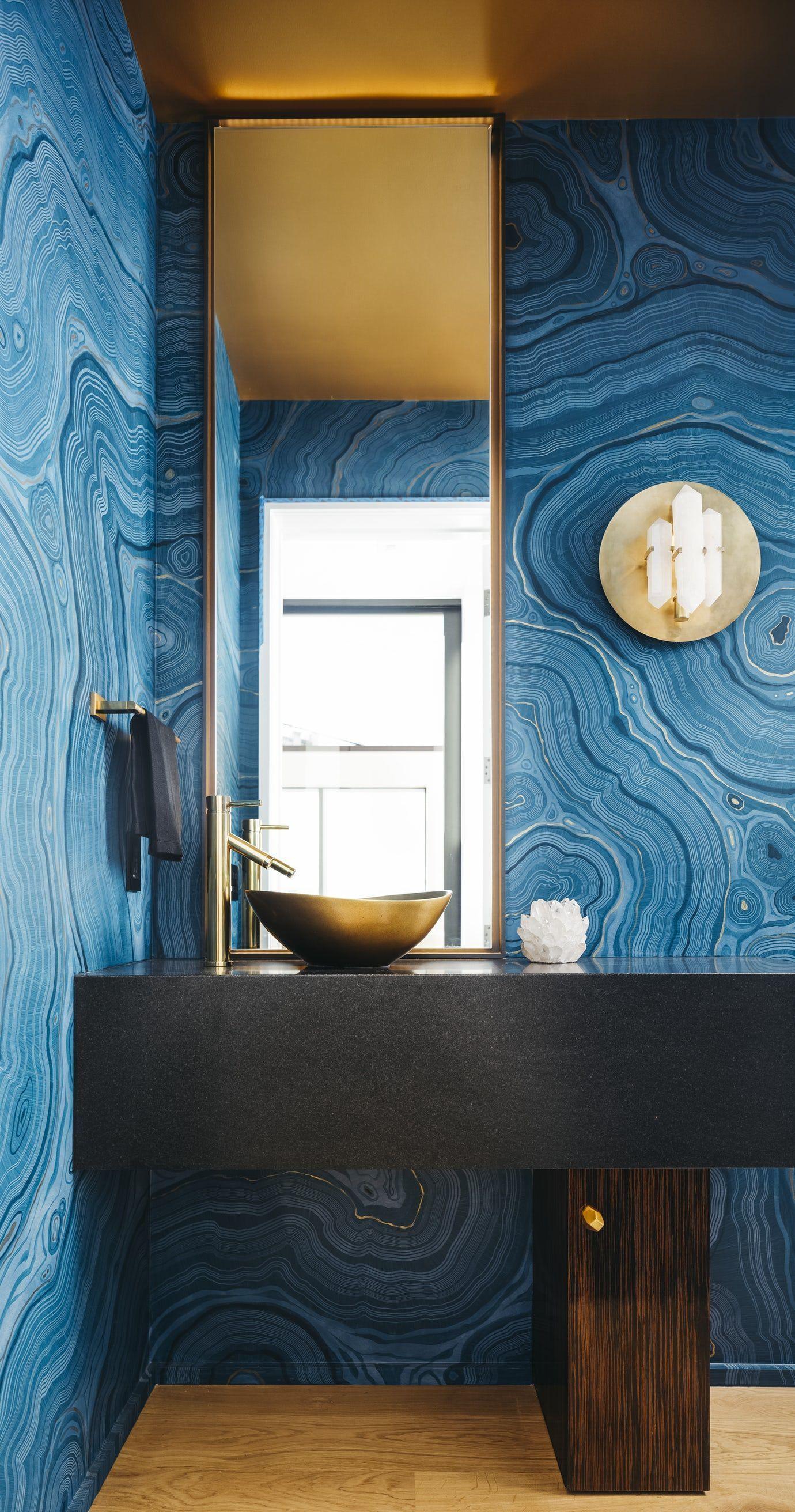 Hình ảnh phòng tắm với giấy dán tường màu xanh vân gỗ ấn tượng, bồn rửa tay bằng đồng sáng bóng