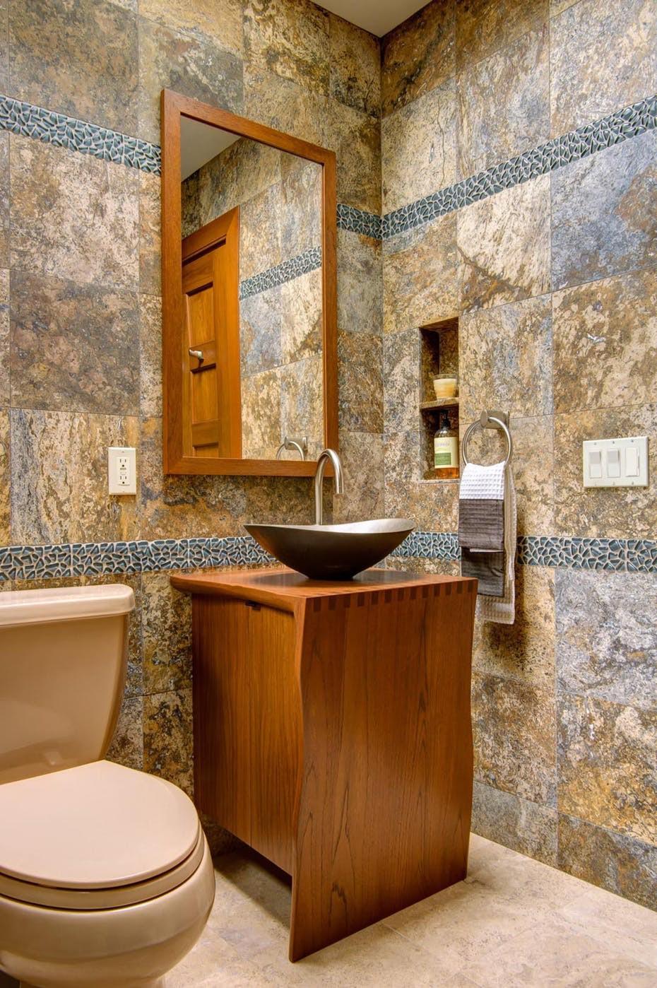 Phòng tắm ốp đá tự nhiên, bồn rửa kim loại đặt trên bệ gỗ