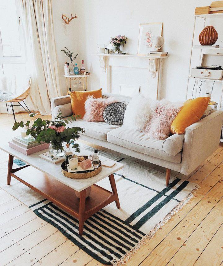 Hình ảnh phòng khách màu be với gối tựa sofa màu vàng, bàn trà chữ nhật, sàn lát gỗ, chậu cây trang trí
