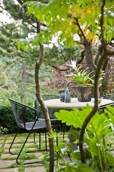 Bàn đá cùng ghế sắt rèn, với điểm nhấn là tượng đá cùng chậu cây hoa trắng sang trọng