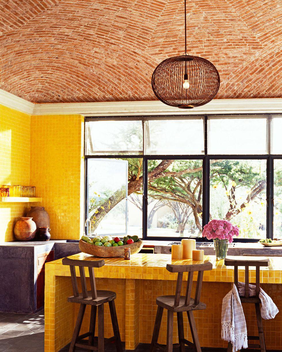 Điểm nhấn của phòng bếp màu vàng chủ đạo chính là những chiếc ghế gỗ mộc mạc.