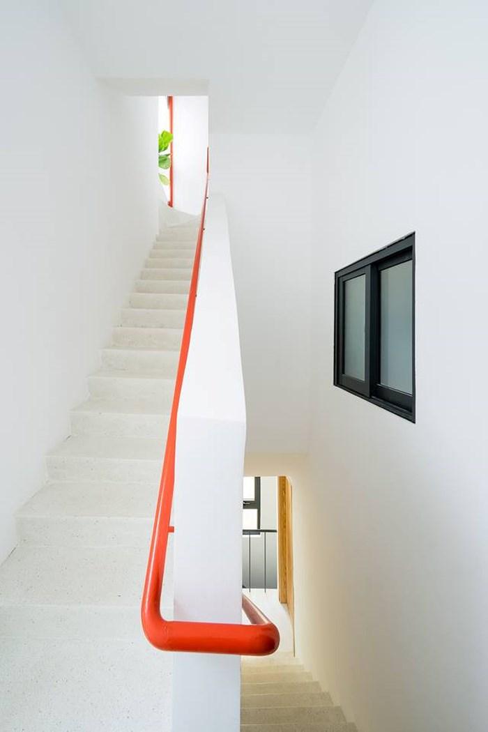 Cầu thang dẫn lối lên các tầng trên công trình nhà chồng nhà nổi bật hơn với tay vịn màu cam.