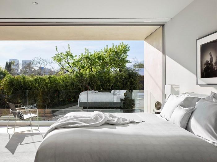 Hai phòng ngủ có tường kính trong suốt được bố trí trên tầng 2 biệt thự.