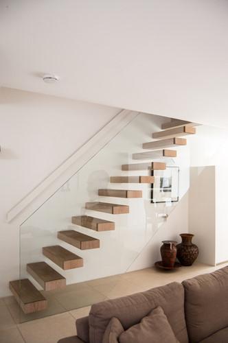 Cầu thang gỗ bậc hở lồng vào lan can bằng kính cường lực