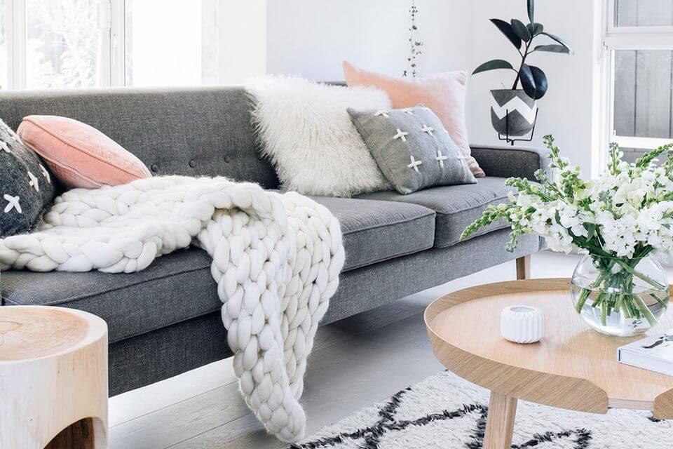 Hình ảnh phòng khách hiện đại với ghế sofa xám, khăn phủ len, đệm lông trắng