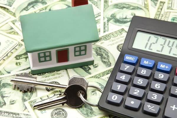 Hình ảnh cận cảnh mô hình ngôi nhà, máy tính cầm tay, chìa khóa, phía dưới là những đồng USD
