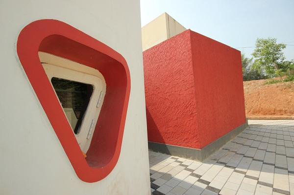 Hình ảnh cận cảnh một mặt bên của trường mẫu giáo với khung cửa kính viền đỏ ấn tượng