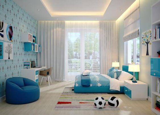 Hình ảnh phòng ngủ dành cho con trai với giường, giấy dán tường, bàn học, kệ sách màu xanh dương, rèm cửa trắng, ghế ngồi thư giãn