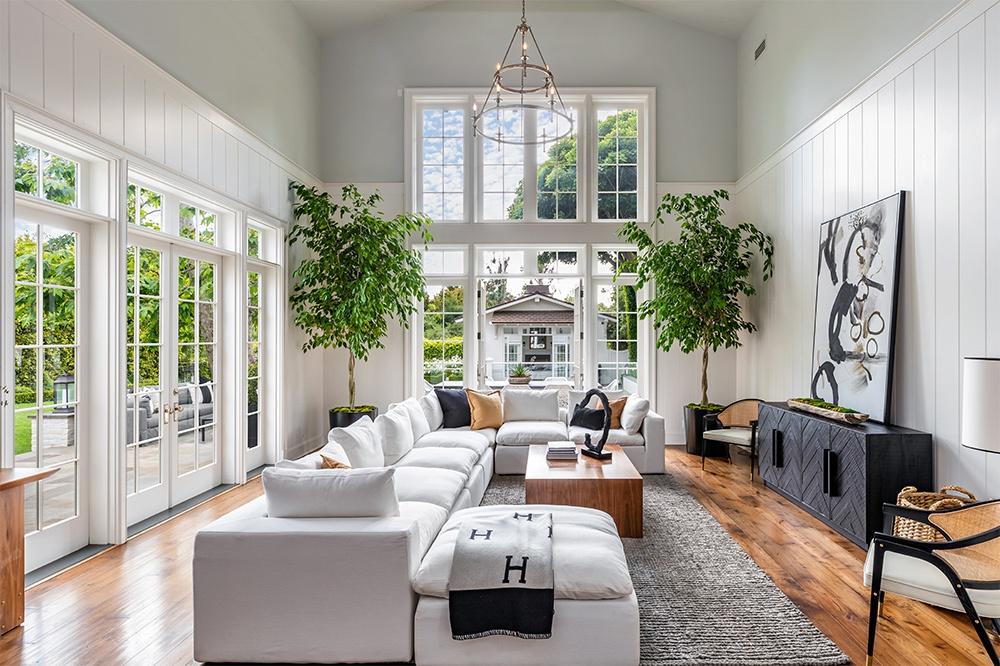 Hình ảnh phòng khách rộng rãi, bài trí cây xanh ở góc, kết nối với hiên nhà qua cửa kính