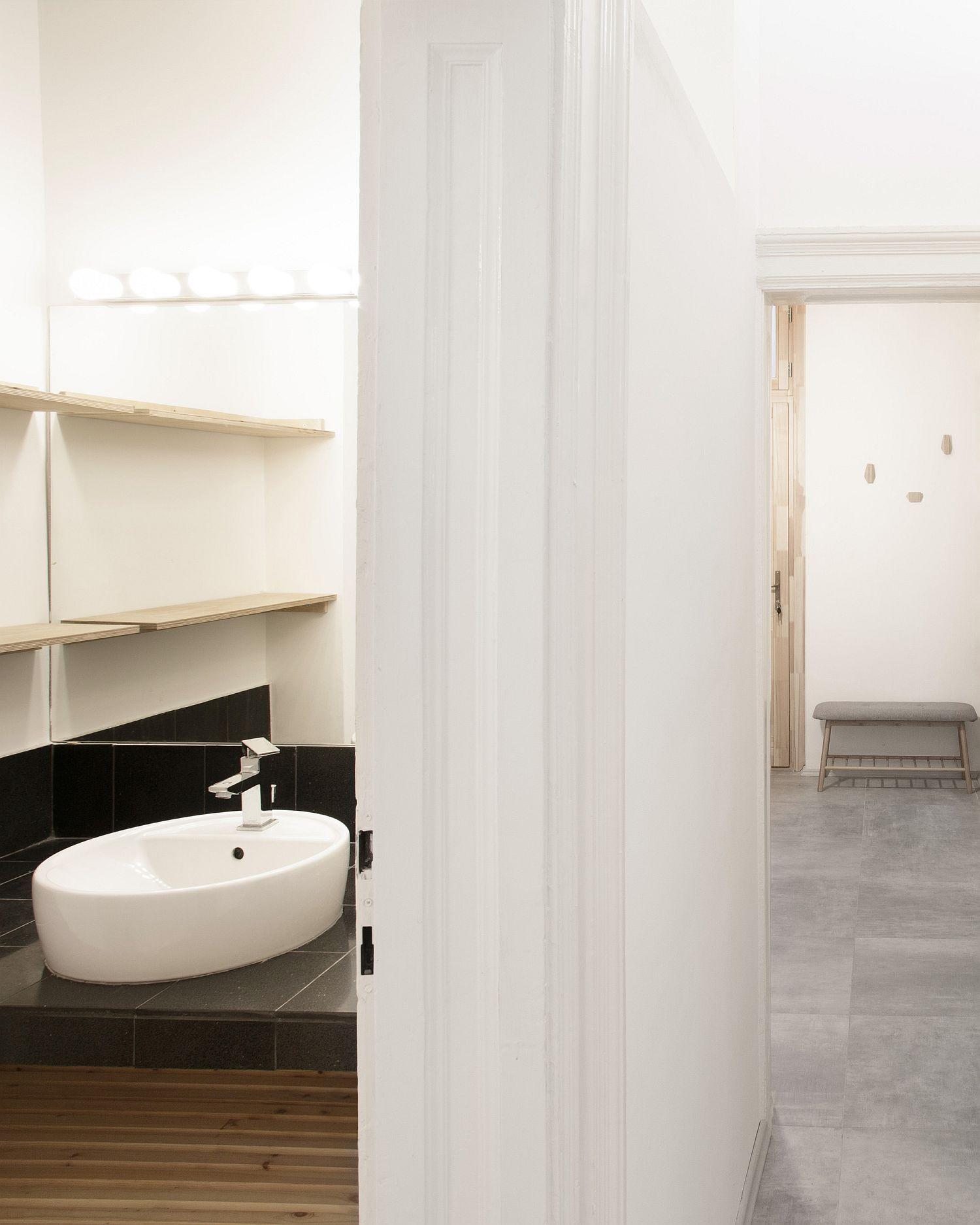 Hình ảnh kệ mở gắn tường cạnh bồn rửa mặt cung cấp không gian lưu trữ gọn đẹp trong phòng tắm.