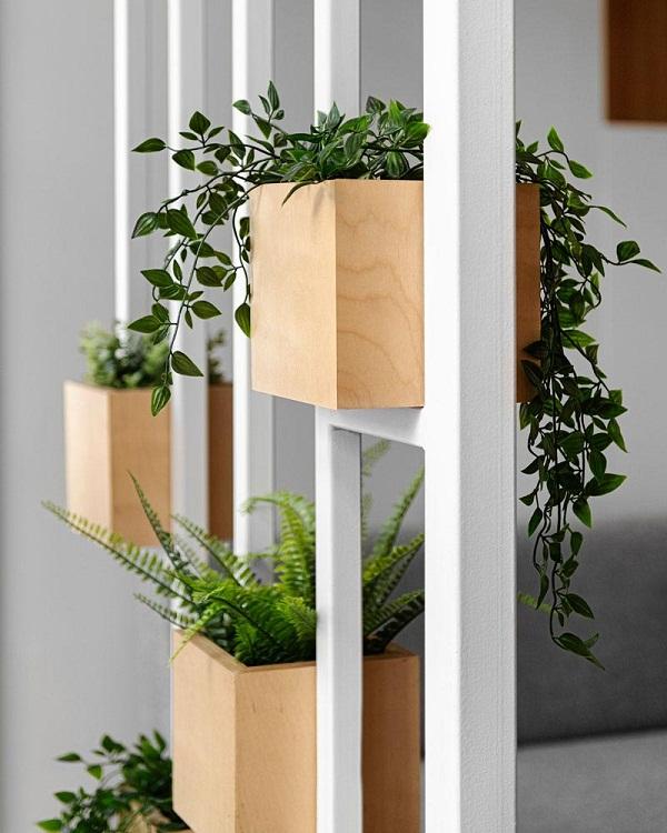 Hình ảnh cây trồng trong chậu gỗ được đặt xen kẽ ở khung thép giúp thanh lọc không khí, đồng thời tạo cảm giác gần gũi với thiên nhiên.
