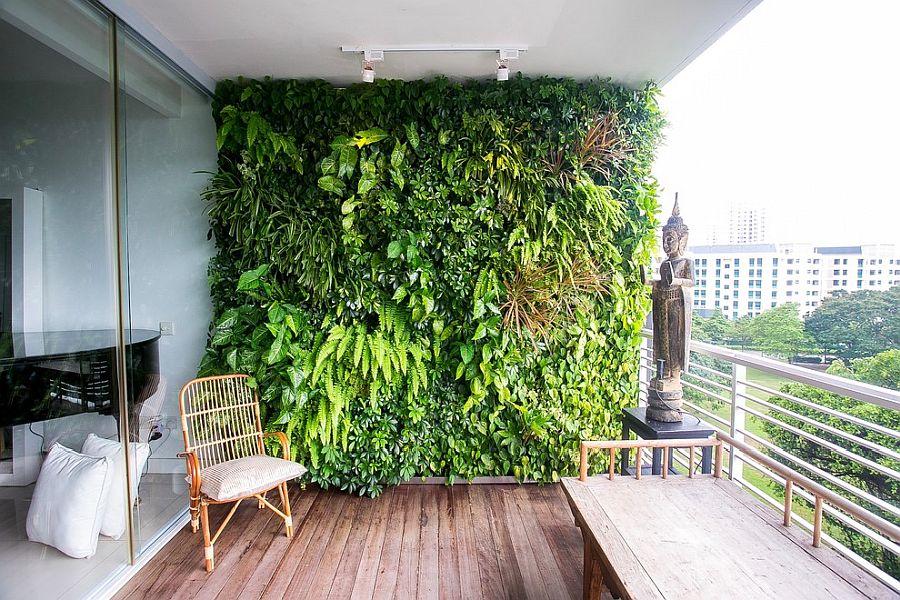 Hình ảnh ban công căn hộ nổi bật với bức tường cây xanh, cửa kính, bàn ghế, sàn gỗ