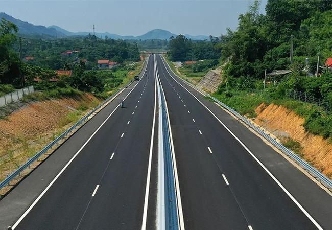 Hình ảnh một đoạn tuyến cao tốc Bắc Giang - Lạng Sơn đã hoàn thiện, thông xe kỹ thuật, hai bên là cây cối, núi rừng, làng mạc