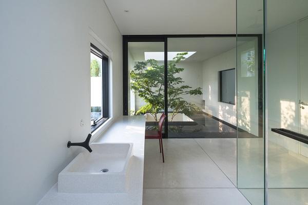 Hình ảnh góc hành lang ngôi nhà với bồn rửa tay bằng sứ, khung cửa sổ kính, ghế ngồi màu đỏ