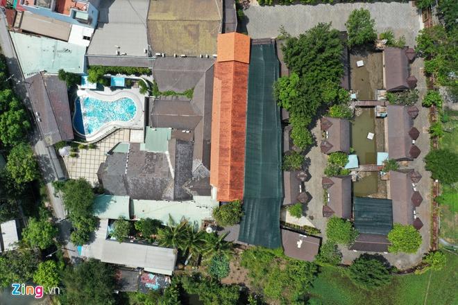 Hình ảnh tổ hơp Gia Trang quán - Tràm Chim resort nhìn từ trên cao với nhà mái mái màu xám, bể bơi, cây xanh xen kẽ