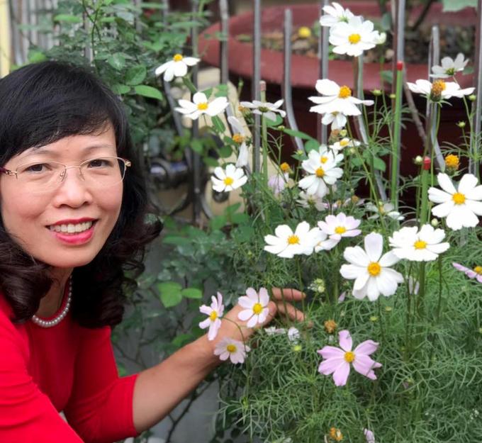 Ảnh chụp chị Thêu bên cạnh khóm hoa bướm trên sân thượng