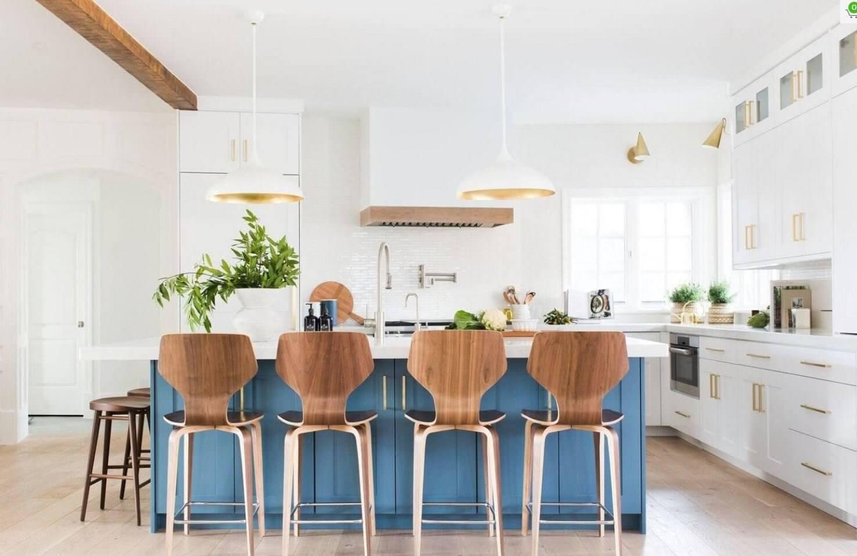 Hình ảnh phòng bếp màu trắng chủ đạo được trang trí bởi những chậu cảnh xanh mướt, đảo bếp màu xanh dương, ghế gỗ