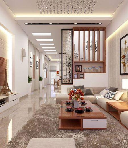 Hình ảnh phòng khách nhà ống 2 tầng hai phòng ngủ được đóng khung bởi bộ ghế sofa da màu trắng sữa kết hợp cùng bàn trà đặt trên thảm lông mềm mại, đối diện là tủ kệ tivi.