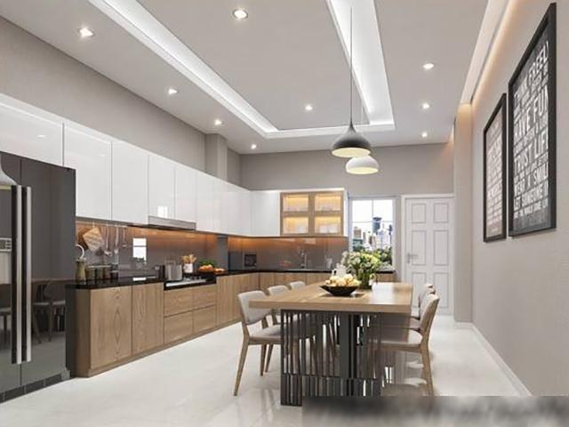 Hình ảnh phòng bếp kết hợp không gian ăn uống sử dụng tông trắng chủ đạo, tủ gỗ cánh phẳng, bàn ăn mặt kính, lọ hoa trang trí