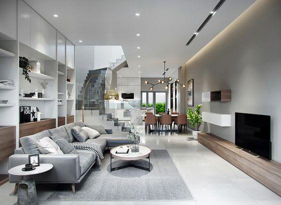 Hình ảnh mẫu phòng khách hiện đại có thiết kế đơn giản với sofa ghi xám kết hợp bàn gỗ tròn, chân kim loại nhỏ xinh đặt trên thảm trải cùng tông, phía sau là tủ kệ cao kịch trần, đối diện là tủ kệ tivi