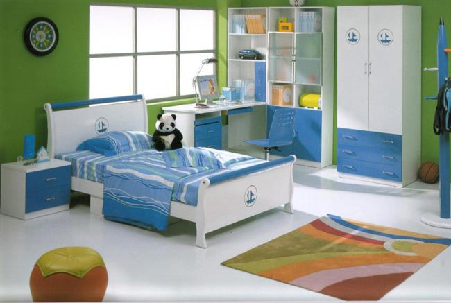 Hình ảnh phòng ngủ cho bé trai với tông xanh lá - xanh dương chủ đạo, tủ kệ lưu trữ, bàn học, giá sách cạnh cửa sổ kính, ghế ngồi thư giãn màu cam, thảm trải sàn màu sắc