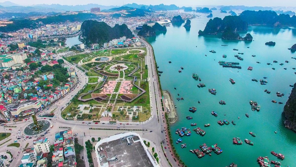 Hình ảnh một góc tỉnh Quảng Ninh nhìn từ trên cao với vịnh biển tấp nập thuyền bè, bên cạnh là loạt khu dân cư thấp tầng, xen kẽ cây xanh công viên