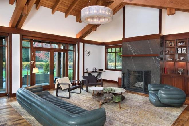 Hình ảnh một phòng khách rộng thoáng với trần ốp gỗ, cửa kính lớn, sofa da