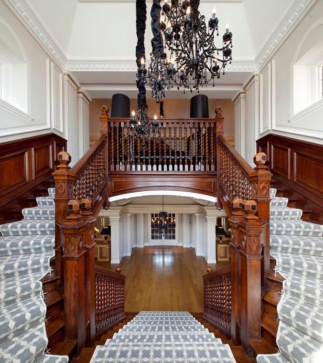 Hình ảnh cận cảnh khu vực cầu thang gỗ sồi cứng, lót thảm màu xám