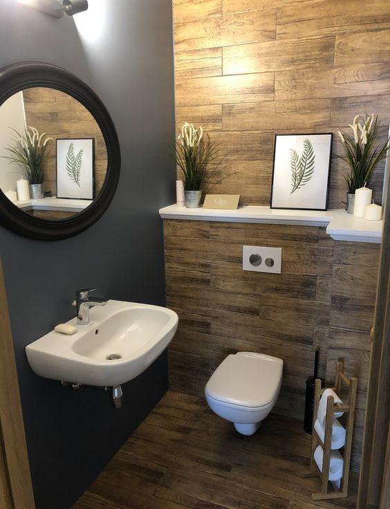 Hình ảnh phòng vệ sinh với sàn lát gỗ, tường màu xám, gương tròn khung đen, bồn cầu, bồn rửa màu trắng, chậu cây trang trí