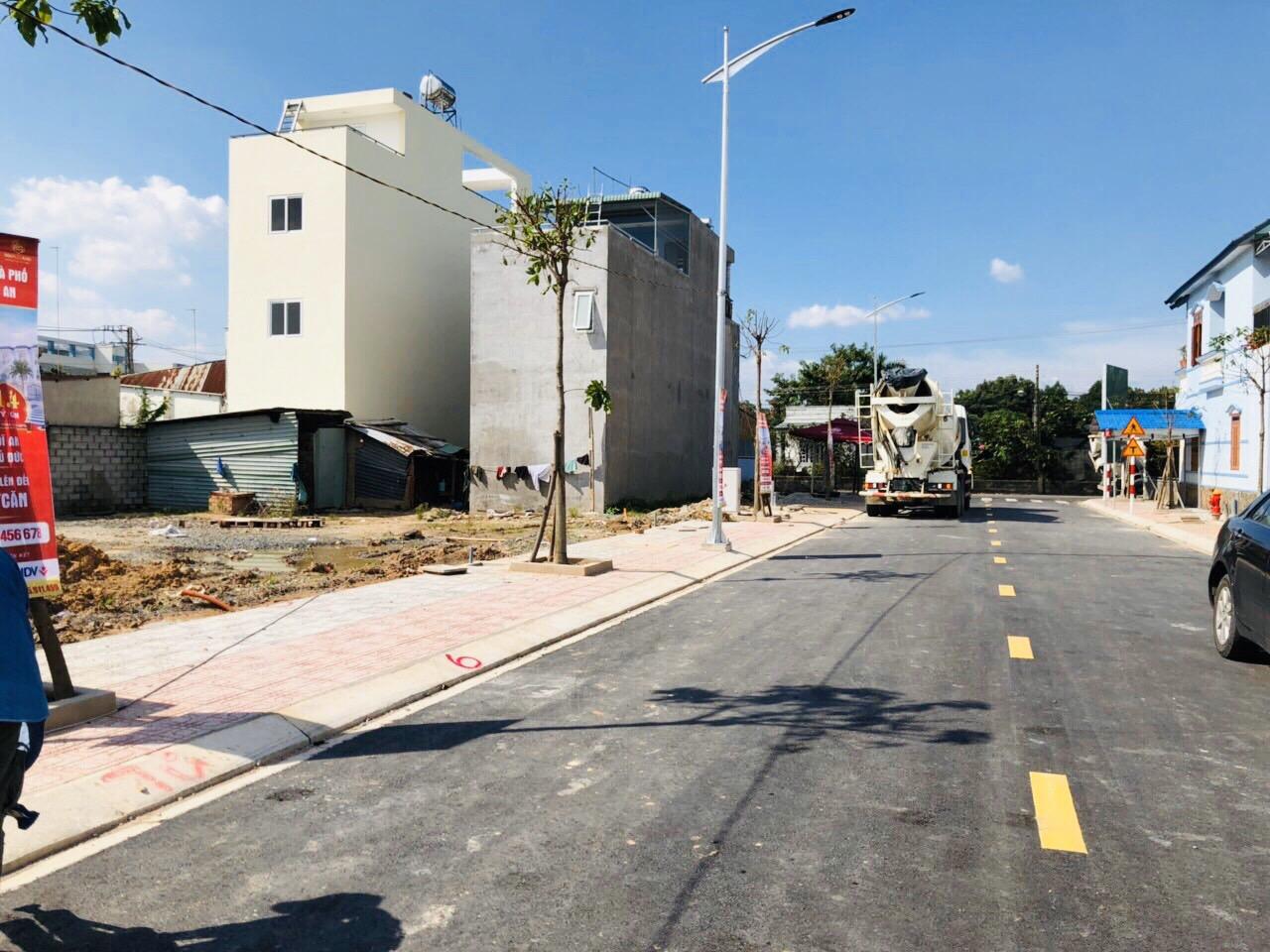 Hình ảnh cận cảnh một con đường mới với vỉa hè lát gạch sạch sẽ, trồng cây xanh, xung quanh nhiều nhà dân