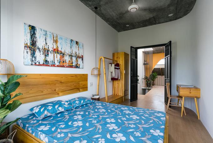 Hình ảnh một phòng ngủ cho người trẻ với trần đen, giường gỗ sáng màu, ga gối màu xanh dương, tranh treo tường..