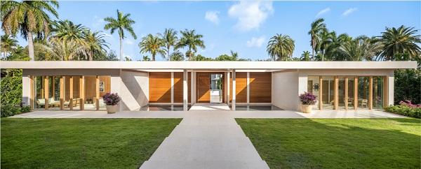 Hình ảnh toàn cảnh mặt tiền biệt thự của siêu mẫu Victoria's Secret với sân cỏ xanh mướt, lối vào bằng bê tông sơn trắng thẳng tắp, xung quanh là hàng dừa xanh tốt