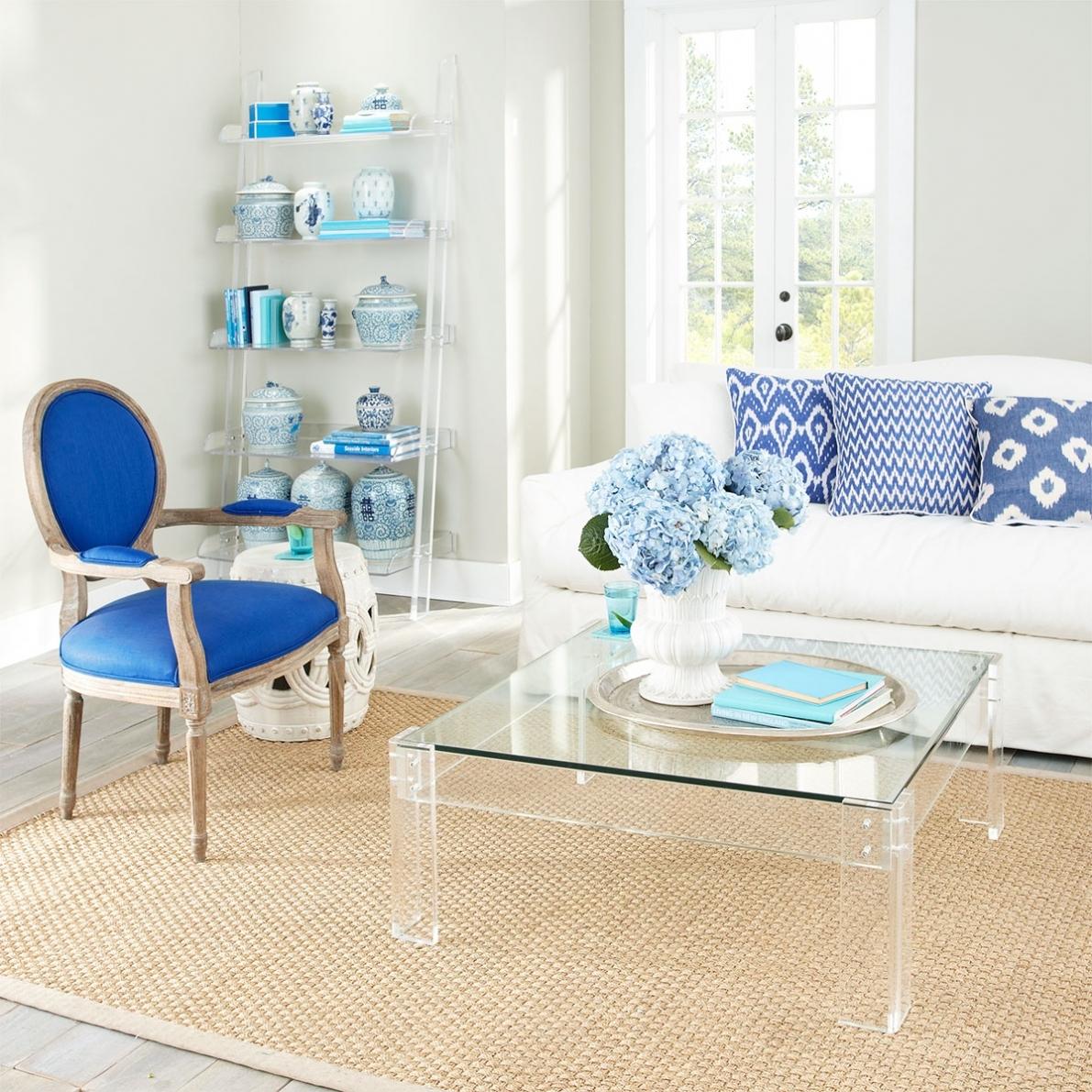 Hình ảnh một phòng khách hiện đại với ghế ngồi bọc nệm màu xanh dương dịu mắt, bàn trà trong suột đặt trên thảm cói, kệ thanh trong suốt ở góc phòng