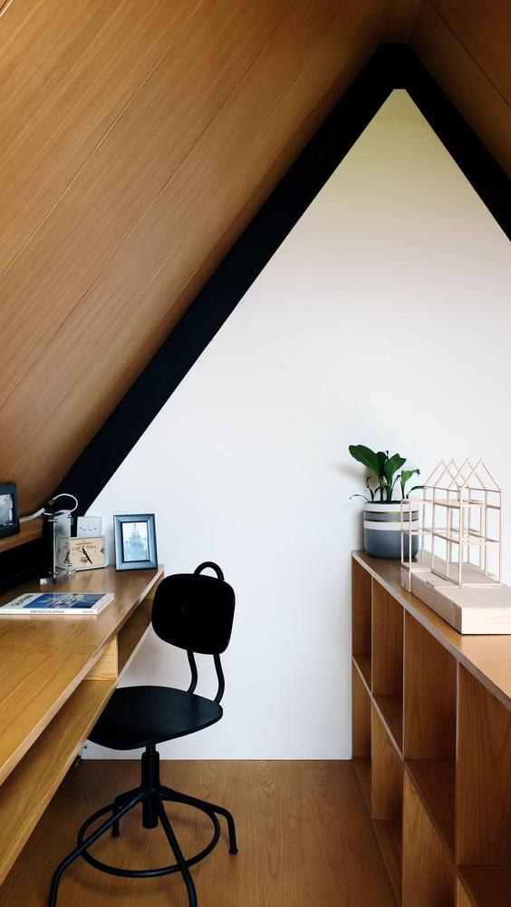 Hình ảnh cận cảnh phòng làm việc trên gác mái với trần ốp gỗ, ghế ngồi màu đen, cửa sổ kính