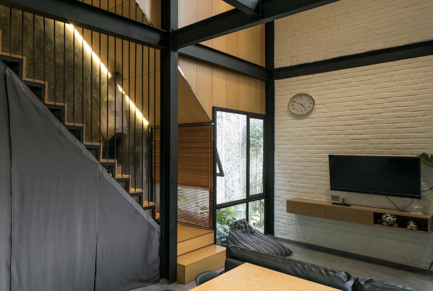Hình ảnh một góc phòng khách với tivi gắn vào bức tường gạch sơn trắng, cạnh đó là cửa kính mở ra khu vườn nhỏ bên ngoài
