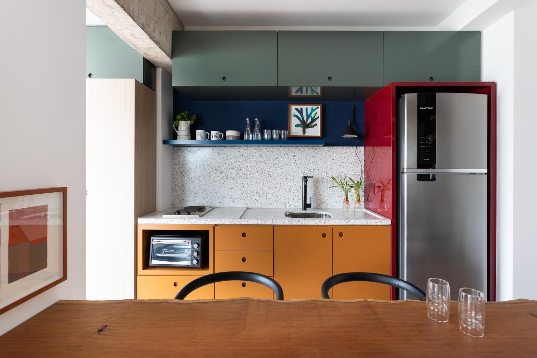 Hình ảnh cận cảnh bàn ăn bằng gỗ thô mộc, ghế sắt màu đen, đèn trang trí kim loại trong phòng bếp