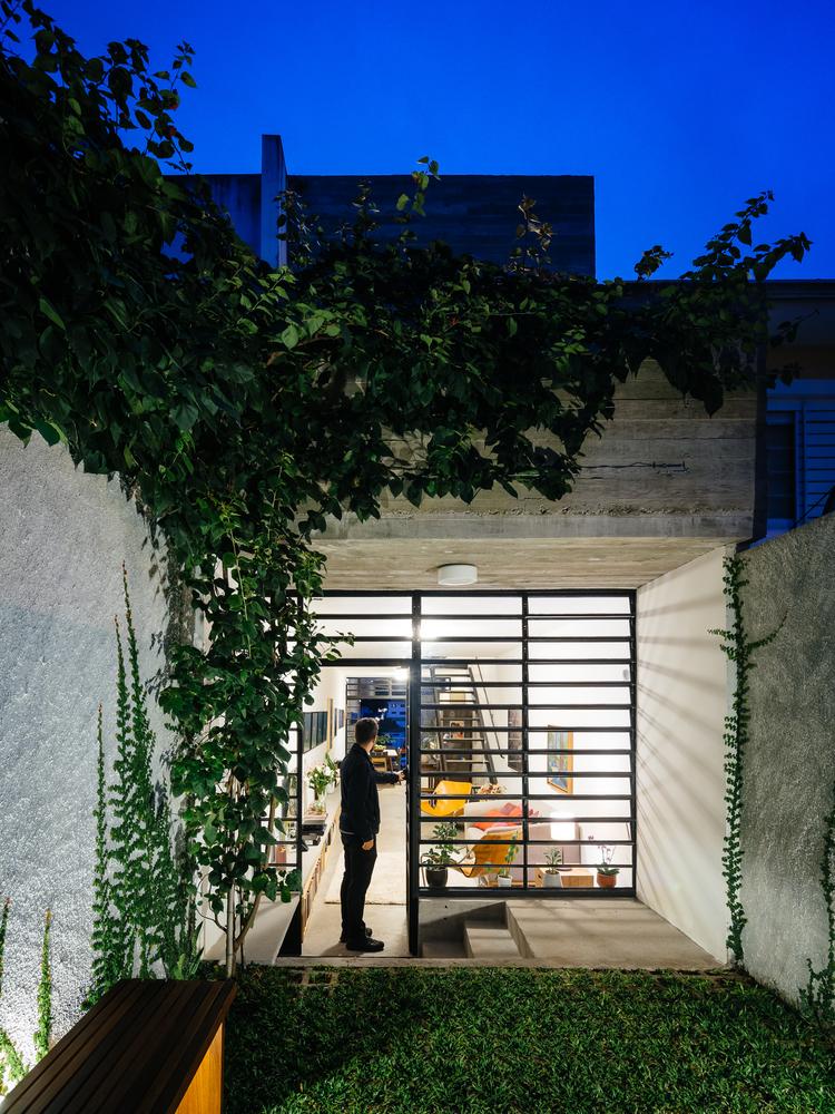 Hình ảnh một người đàn ông đứng ở khung cửa kính mở ra sân vườn xanh mát sau nhà