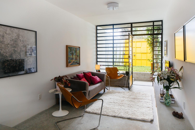 Phòng khách có thiết kế đơn giản với sofa nâu đặt sát tường, hai bên là ghế ngồi thư giãn độc đáo, phía trước đặt thảm lông màu trắng mềm mại.