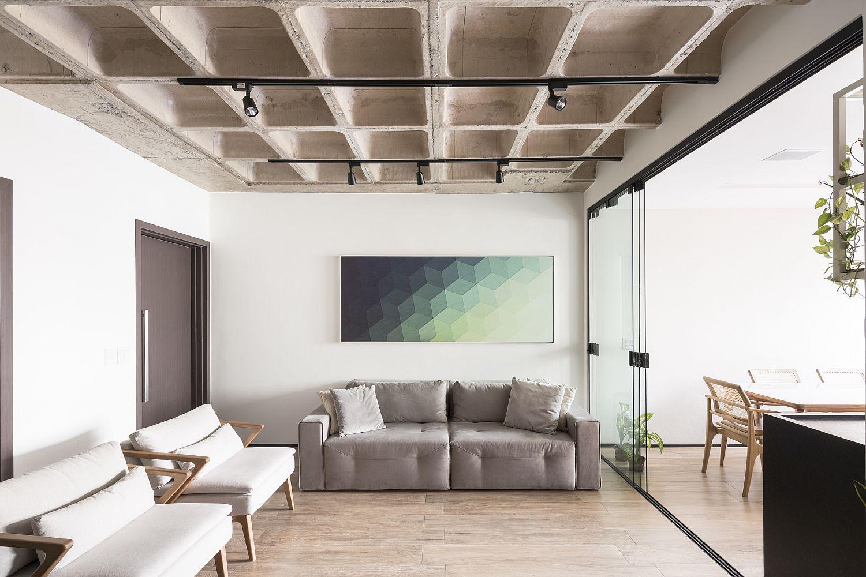 Hình ảnh một phòng khách màu trung tính chủ đạo, tường bê tông độc đáo, ghế sofa xám, cạnh đó là 2 ghế bành thư giãn, tranh nghệ thuật treo tường