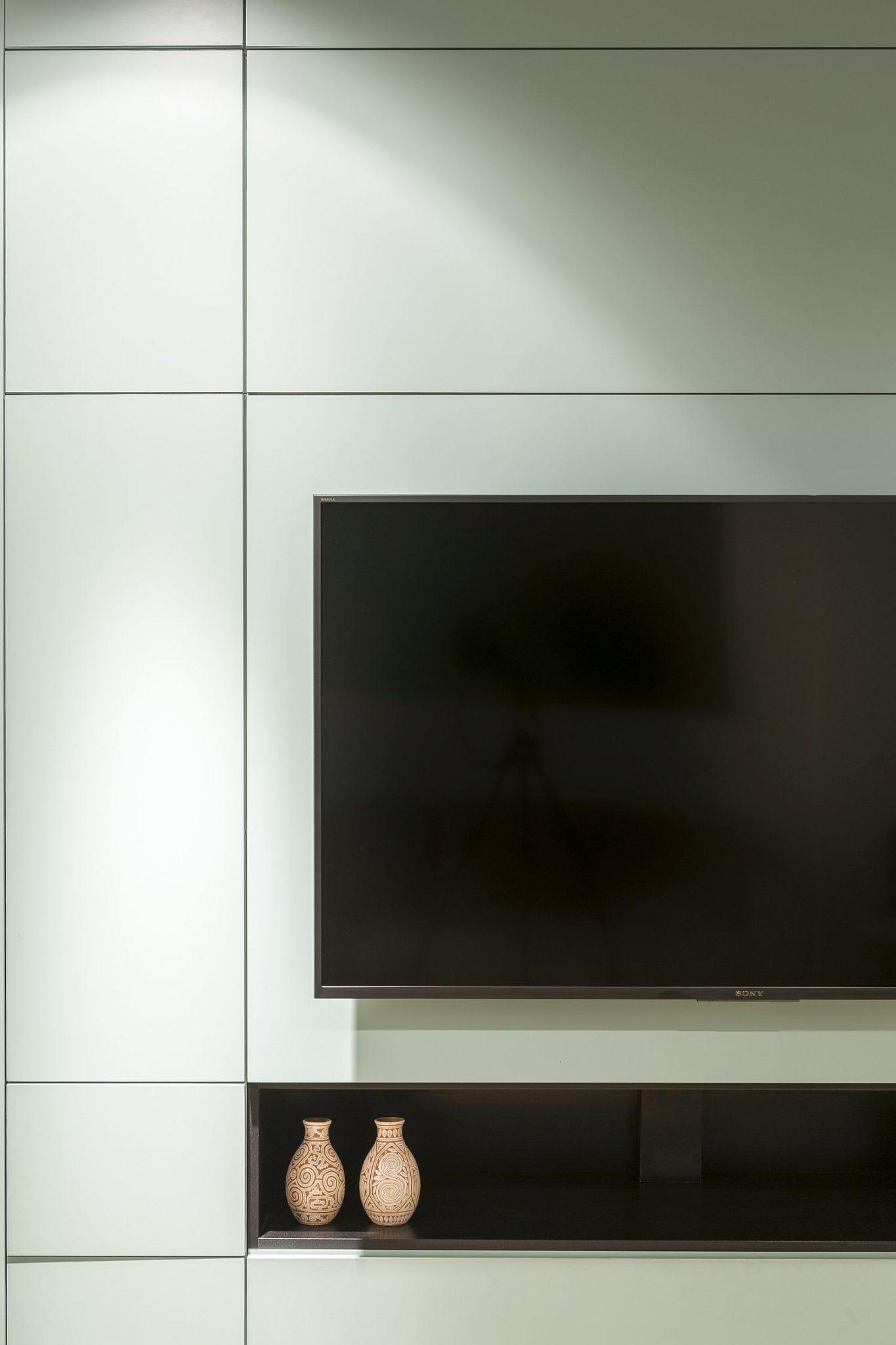 Hình ảnh cận cảnh hệ tủ đa năng màu xanh lá trong căn hộ, nơi đặt tivi, bình trang trí