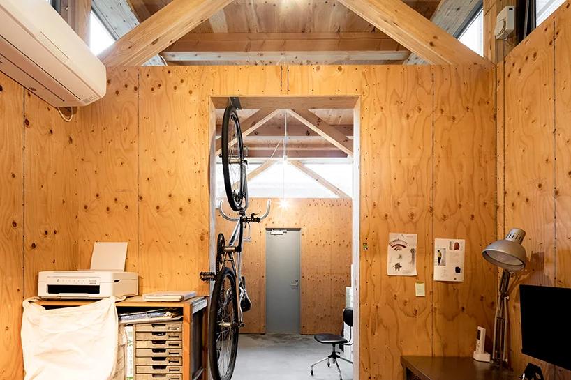 Hình ảnh bên trong phòng làm việc với tường, trần ốp gỗ, bàn làm việc, xe đạp treo, máy in