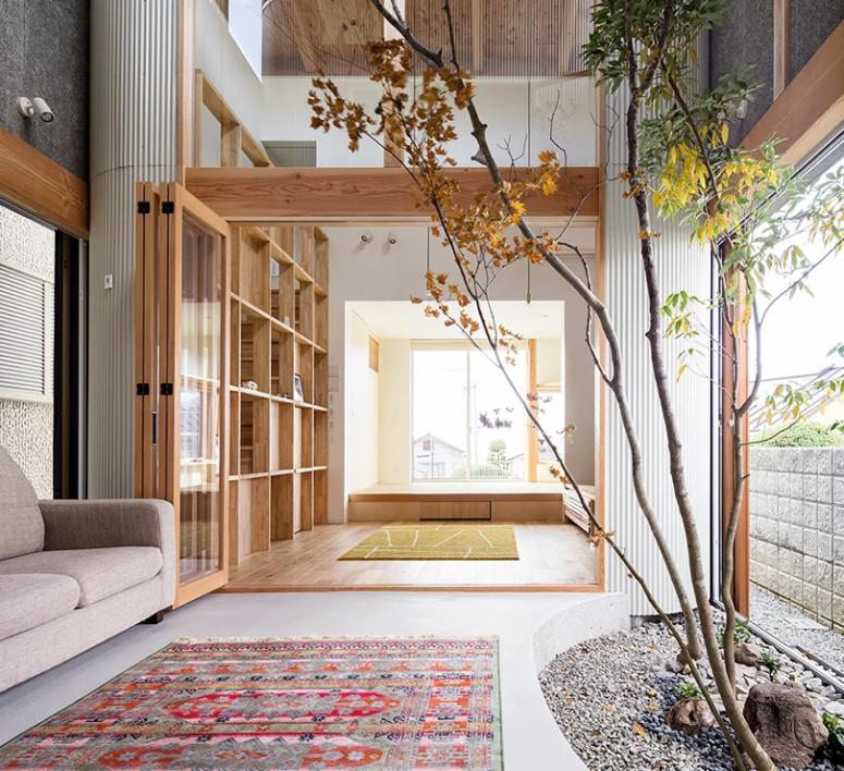 Hình ảnh phòng khách và hệ giá sách bằng gỗ được bố trí ngay dưới khoảng thông tầng, giếng trời, các ô lấy sáng trên cao