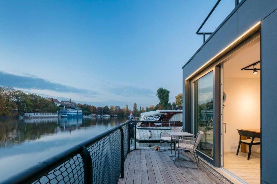 Hình ảnh cận cảnh ban công nhà thuyền với ghế ngồi thư giãn,sàn lát gỗ, lan can căng lưới an toàn