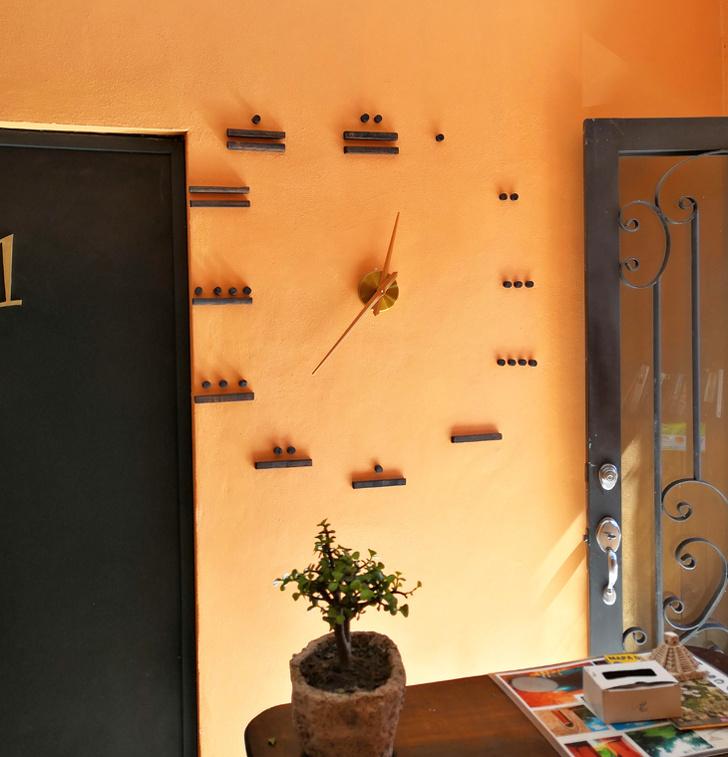 Cận cảnh mẫu đồng hồ hệ số Maya gắn trên bức tường màu cam