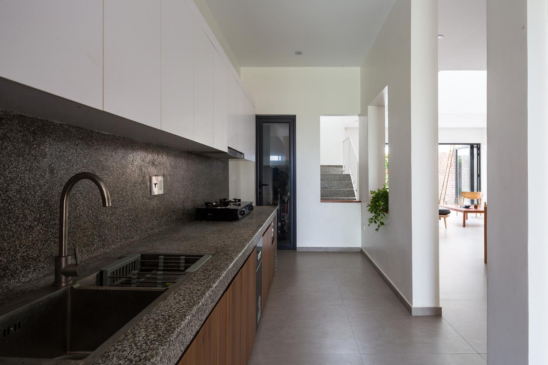 Một góc phòng bếp với hệ tủ màu trắng, bàn bếp bằng đá granite